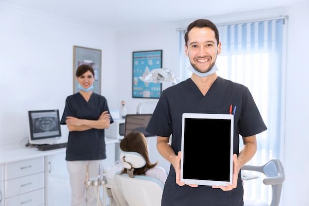Sorrindo, macho, odontólogo, mostrando, tablete digital, em, clínica Foto gratuita