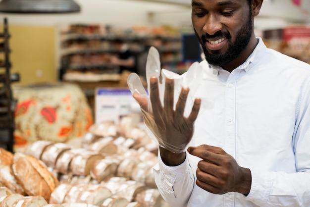 Sorrindo, macho preto, pôr, luva, em, mercearia, loja, comprar, pão Foto gratuita