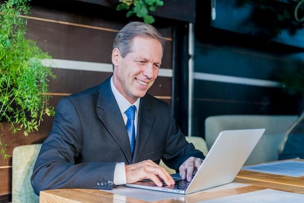 Sorrindo, maduras, homem negócios, trabalhando, laptop, sobre, escrivaninha, em, restaurante Foto gratuita