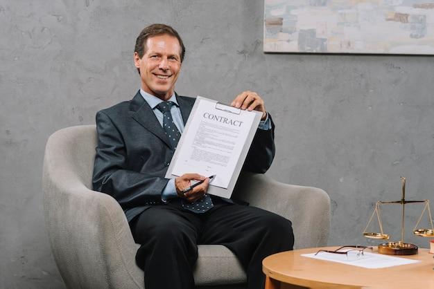 Sorrindo, maduro, advogado, pena segurando, apontar, assinatura, lugar, ligado, um, contrato, documento Foto gratuita