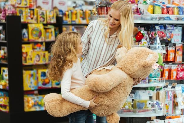 Sorrindo, mãe e filha em pé no supermercado Foto gratuita