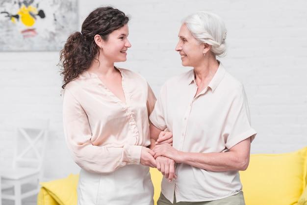 Sorrindo mãe e filha segurando a mão do outro em casa Foto gratuita