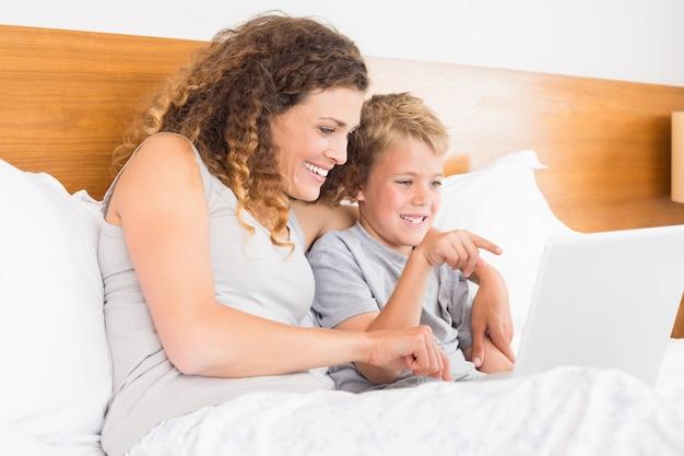 Sorrindo mãe e filho sentado na cama olhando laptop Foto Premium