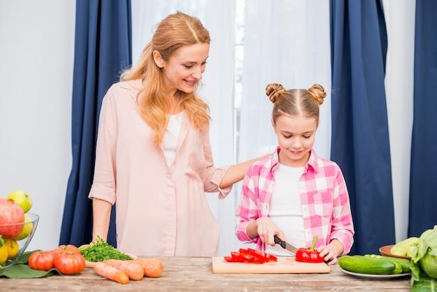 Sorrindo, mãe, olhar, dela, filha, corte, a, pimentão bell, com, faca, ligado, tabela Foto gratuita
