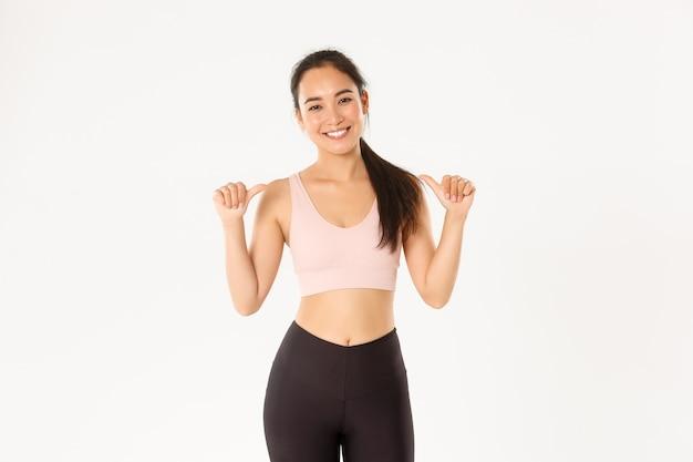 Sorrindo magro e forte, atraente preparador físico feminino asiático, instrutor pessoal ou treinador apontando para si mesma, o logotipo do ginásio, fundo branco. Foto Premium