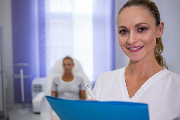 Sorrindo médica segurando relatórios médicos Foto gratuita