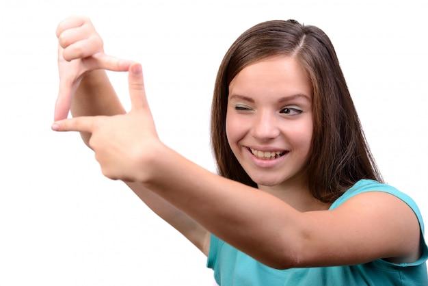 Sorrindo, menina adolescente, fazendo um quadro, com, dela, dedos Foto Premium
