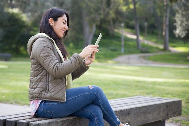 Sorrindo menina alegre, desfrutando de conexão sem fio no parque da cidade Foto gratuita