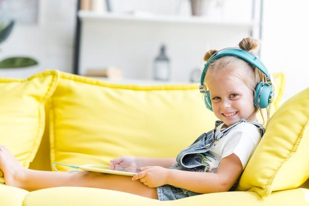 Sorrindo menina bonitinha em fones de ouvido ouvir música usando um tablet Foto gratuita