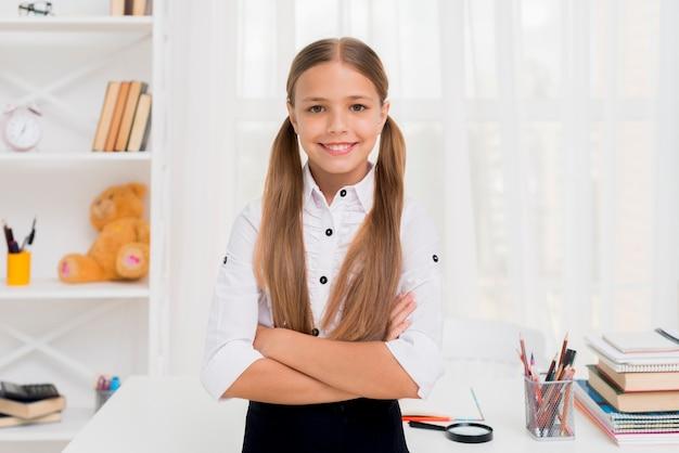 Sorrindo, menina elementar escola, ficar, com, braços cruzaram Foto gratuita