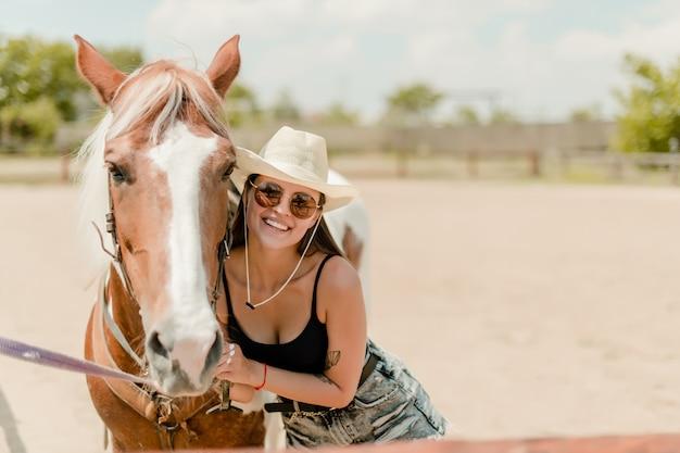 Sorrindo, menina rural, em, chapéu vaqueiro, com, dela, cavalo, ligado, um, fazenda Foto Premium