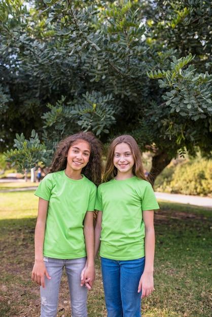 Sorrindo, meninas, ficar, frente, árvore, parque Foto gratuita