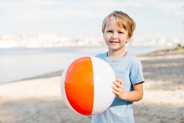 Sorrindo, menino, carregar, esfera praia Foto gratuita