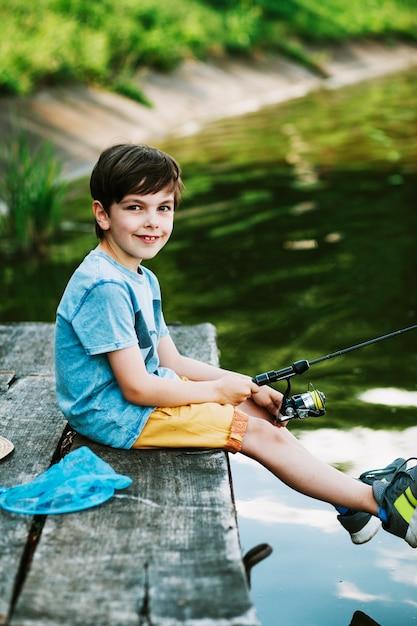 Sorrindo, menino sentando, ligado, cais, pesca, sobre, a, lago Foto gratuita