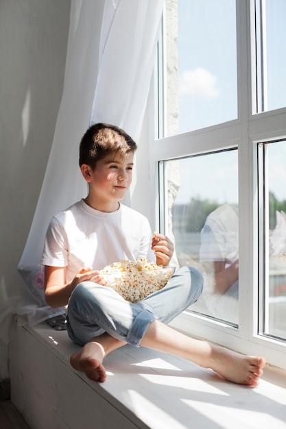 Sorrindo, menino sentando, ligado, peitoril janela, segurando, tigela pipoca, e, olhar, exterior Foto gratuita