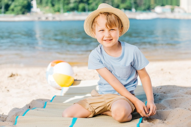 Sorrindo, menino sentando, ligado, tapete, ligado, costa areia Foto gratuita