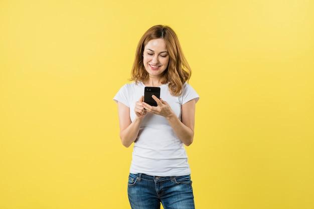 Sorrindo mensagens de mensagens de texto jovem loira no telefone móvel contra um fundo amarelo Foto gratuita
