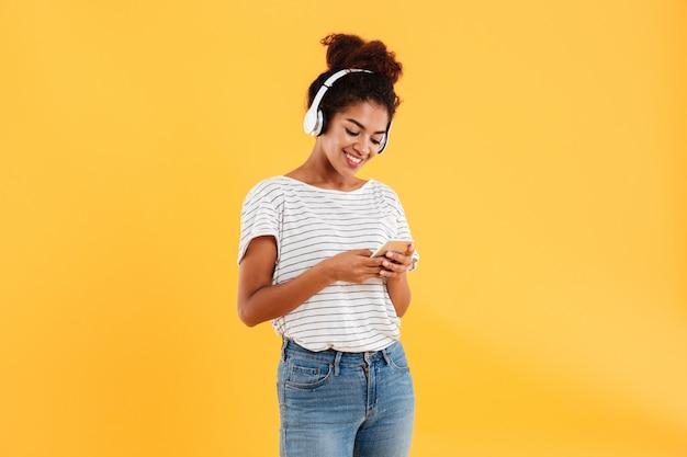 Sorrindo mulher africana, ouvindo música e usando o telefone Foto gratuita
