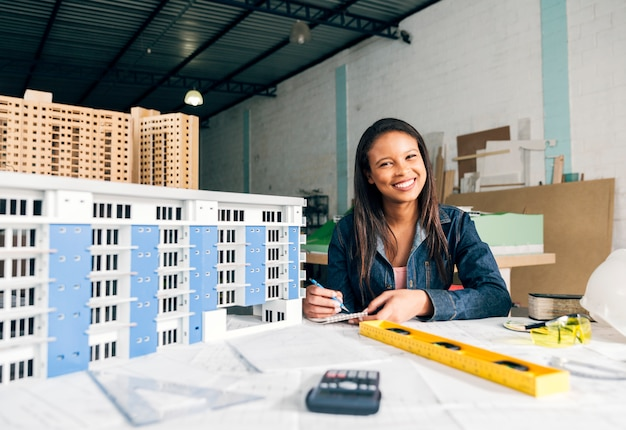 Sorrindo, mulher africano-americana, notas levando, perto, modelo, de, predios Foto gratuita