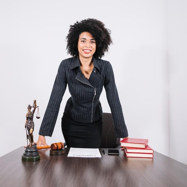 Sorrindo, mulher americana africana, perto, tabela, com, smartphone, livros, documento, e, estátua Foto Premium