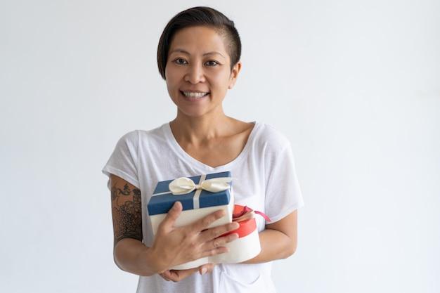 Sorrindo, mulher asian, segurando, dois, caixas presente Foto gratuita