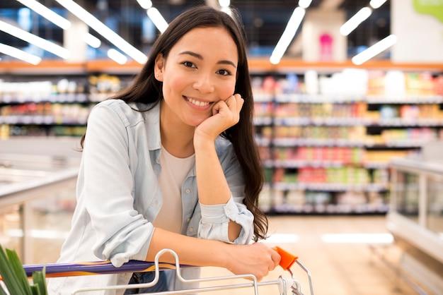 Sorrindo mulher asiática com carrinho de compras no supermercado Foto Premium