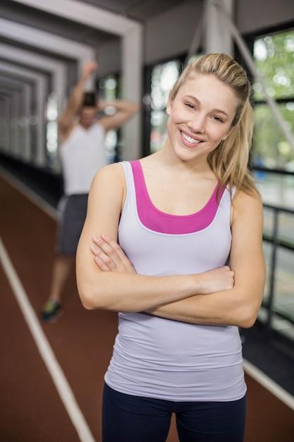 Sorrindo mulher atlética posando com os braços cruzados na pista Foto Premium