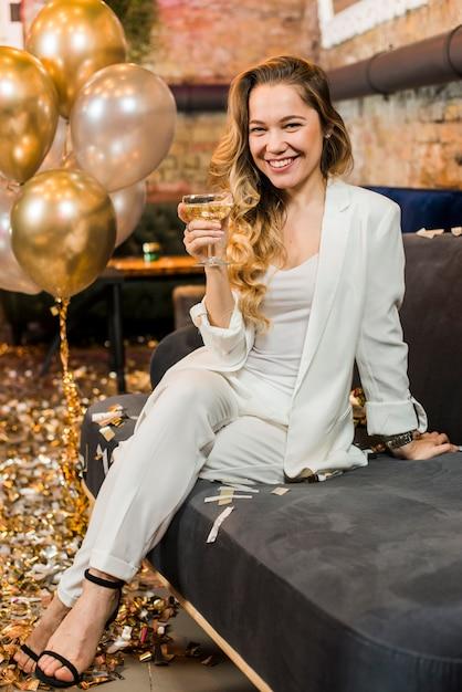 Sorrindo, mulher bonita, com, vidro, de, uísque, sentar sofá Foto gratuita