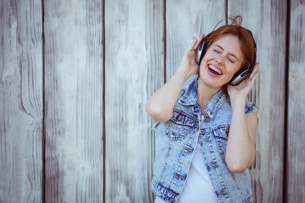 Sorrindo, mulher hipster, cupping, dela, orelhas, escutar música alta, através, fones Foto Premium