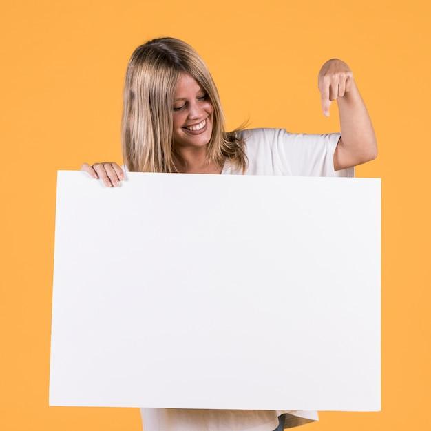 Sorrindo, mulher jovem, apontar, dedo indicador, em, branca, em branco, painél public Foto gratuita