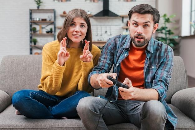 Sorrindo, mulher jovem, com, dedos cruzados, sentando, perto, a, homem, videogame jogo Foto gratuita