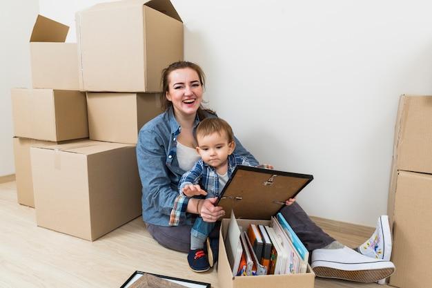 Sorrindo, mulher jovem, com, dela, filho, sentando, em, dela, casa nova, com, caixas cartão Foto gratuita