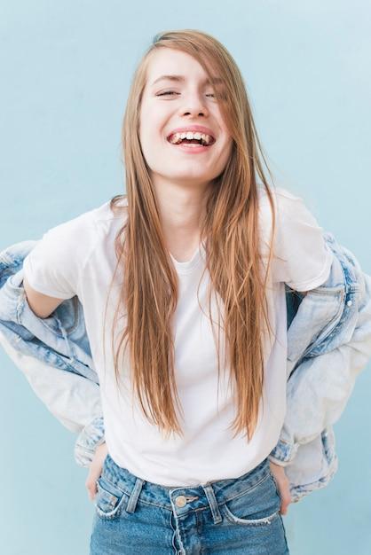Sorrindo, mulher jovem, com, longo, cabelo loiro, ficar, ligado, azul, fundo Foto gratuita