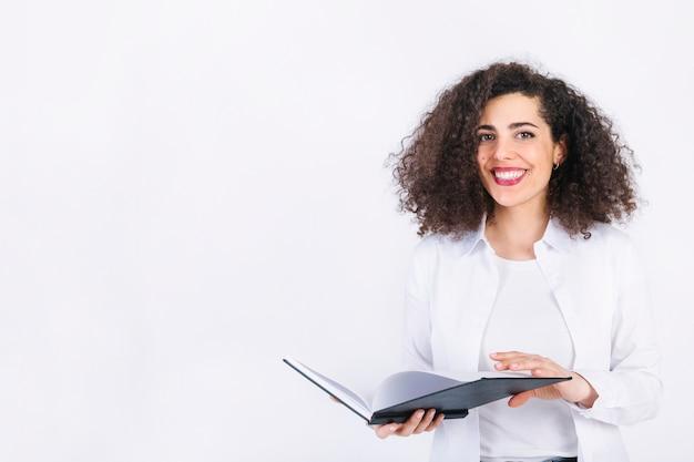 Sorrindo, mulher jovem, com, notepad Foto gratuita