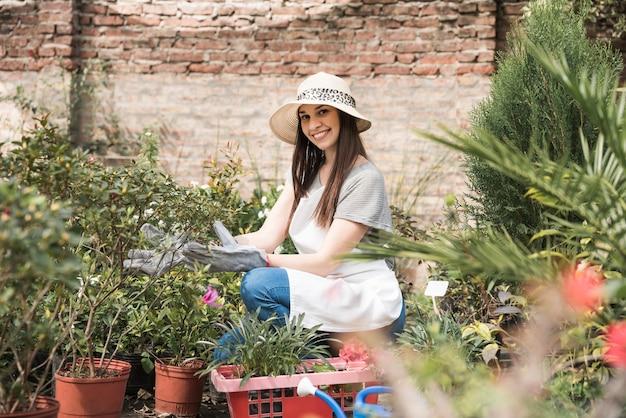 Sorrindo, mulher jovem, crouching, em, berçário, perto, plantas Foto gratuita