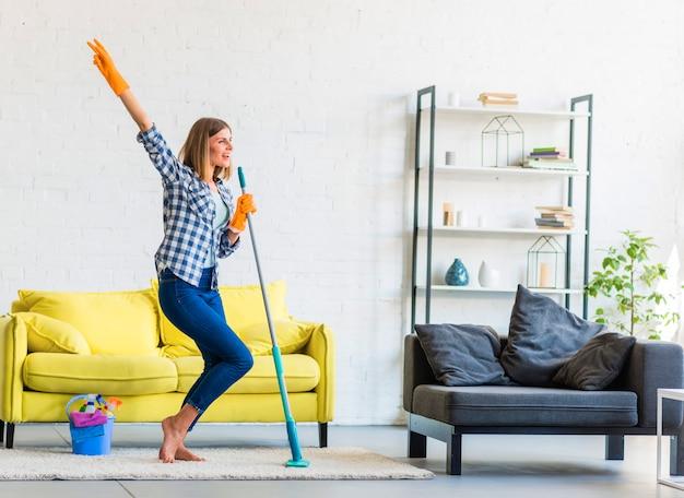 Sorrindo, mulher jovem, dançar, em, a, sala de estar, com, limpeza, equipamentos Foto gratuita