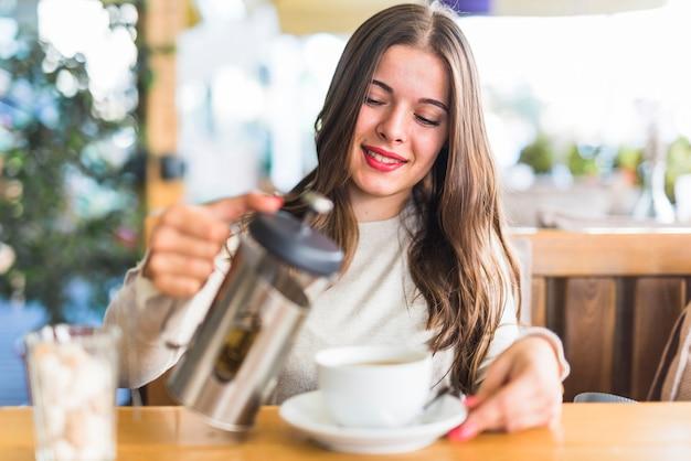 Sorrindo, mulher jovem, despejar, chá herbário, em, a, copo Foto gratuita