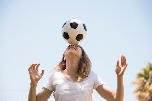 Sorrindo, mulher jovem, equilibrar, bola futebol, testa Foto gratuita