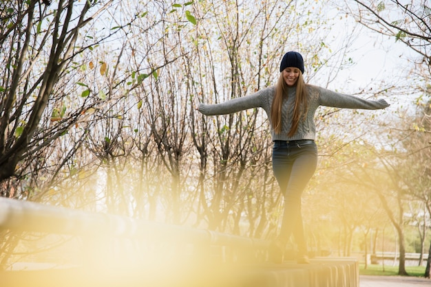 Sorrindo, mulher jovem, equilibrar, parque Foto gratuita
