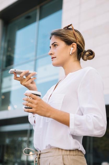 Sorrindo, mulher jovem, falando telefone esperto, com, alto-falante Foto gratuita