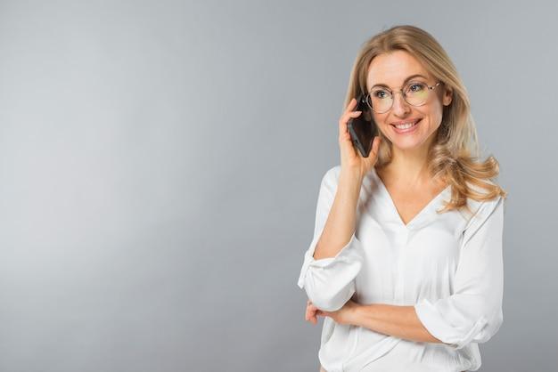 Sorrindo, mulher jovem, falando telefone móvel, contra, cinzento, fundo Foto gratuita
