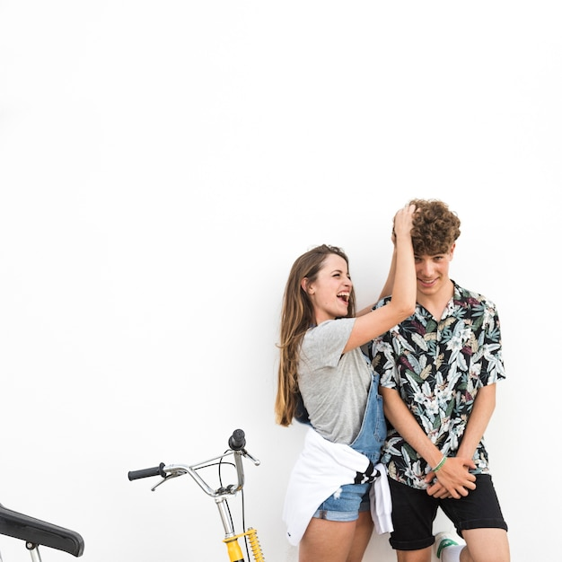 Sorrindo, mulher jovem, fazendo divertimento, com, dela, namorado, ficar, com, bicicleta, contra, branca, fundo Foto gratuita