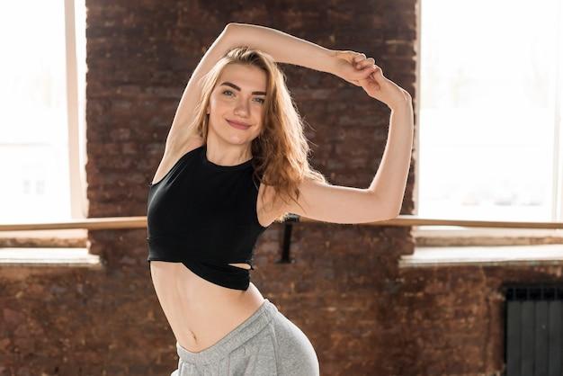 Sorrindo, mulher jovem, ficar, contra, parede tijolo, esticar, seu, mão Foto gratuita