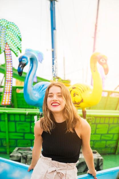 Sorrindo, mulher jovem, ficar, frente, chafariz, em, parque divertimento Foto gratuita