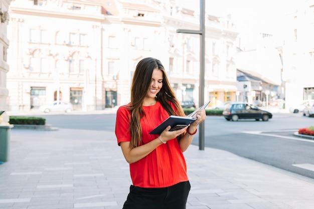 Sorrindo, mulher jovem, ficar, ligado, calçada, leitura, diário Foto gratuita