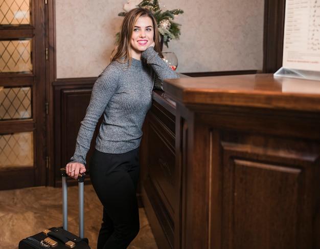 Sorrindo, mulher jovem, ficar, perto, a, escrivaninha recepção, em, hotel Foto gratuita