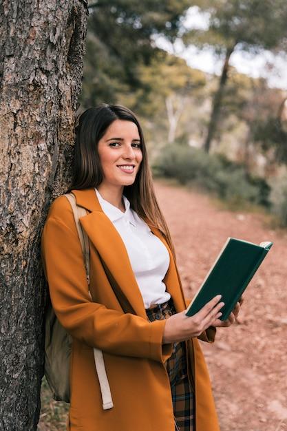 Sorrindo, mulher jovem, inclinar-se, árvore, segurando livro, em, mão Foto gratuita