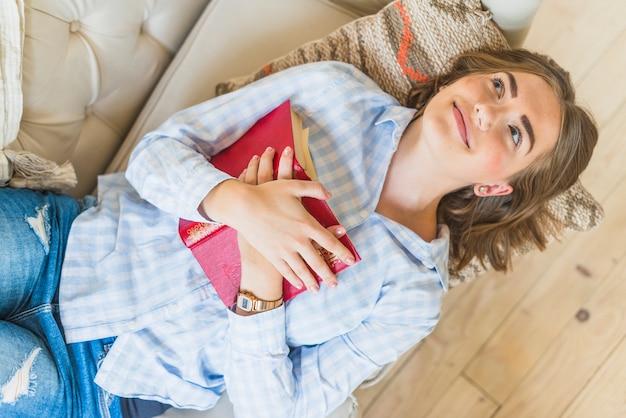 Sorrindo, mulher jovem, mentindo, ligado, sofá, com, livro Foto gratuita
