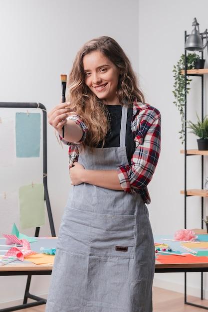 Sorrindo, mulher jovem, mostrando, pretas, pincel Foto gratuita