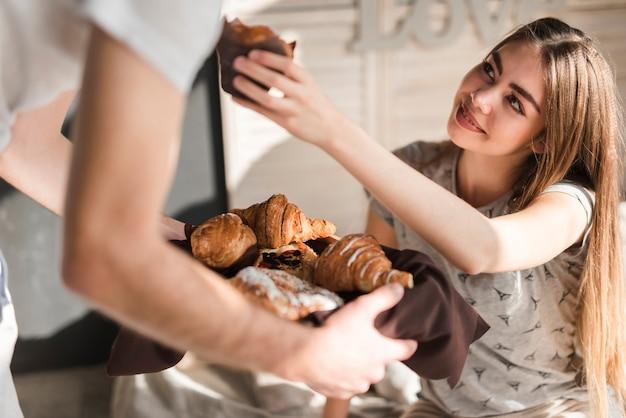 Sorrindo, mulher jovem, oferecendo, bolo copo, para, dela, namorado, segurando, croissant, bandeja Foto gratuita